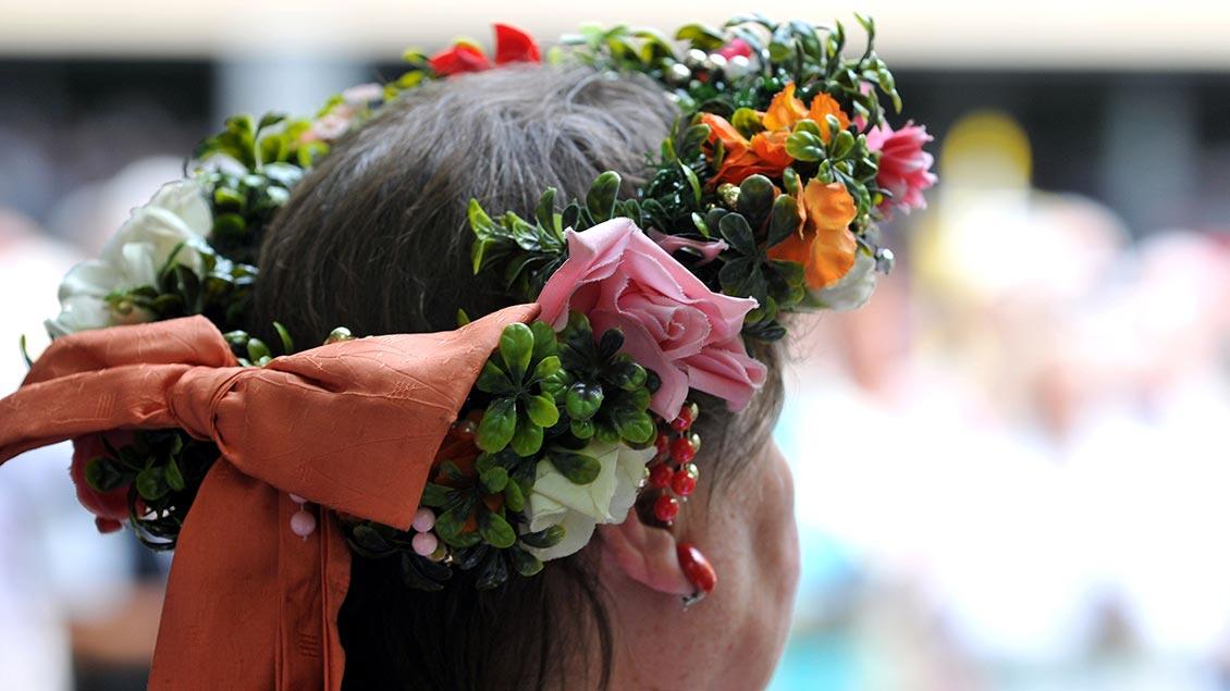 Eine Frau trägt einen Blumenkranz in den Haaren.