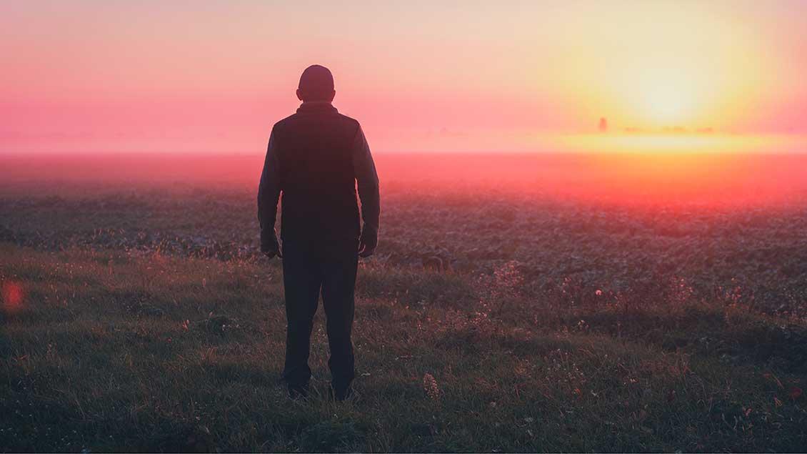 Ein Mann steht vor einem Sonnenuntergang.