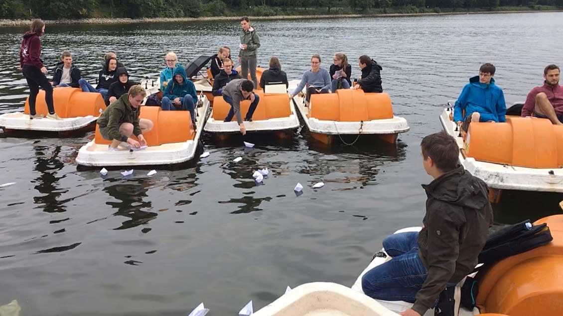 Jugendliche in Tretbooten auf dem Halterner Stausee lassen Papierschiffchen zu Wasser.
