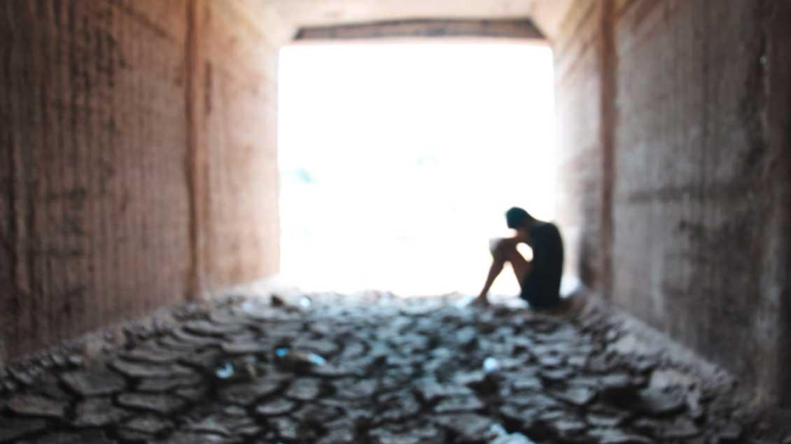 Ein Mensch sitzt im Dunkeln auf dem Boden Symbol-Foto: pimchawee (Shutterstock)