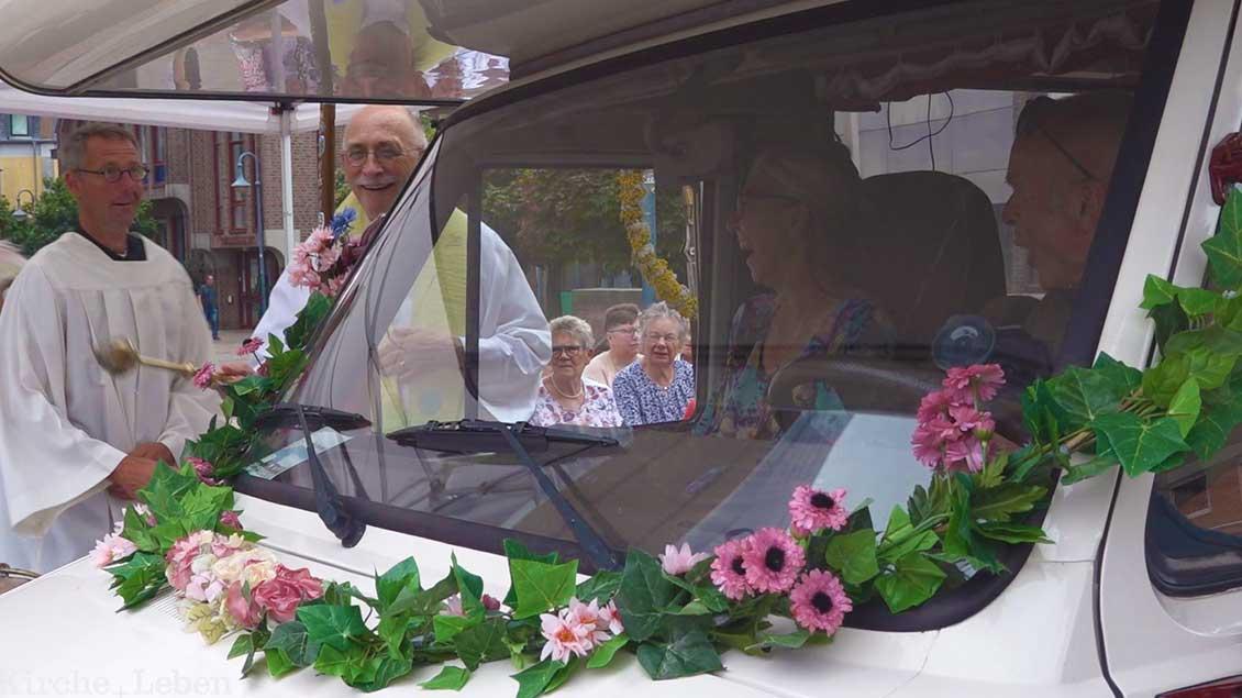 Pater Hans Peters steht am Fenster des Reisemobils und besprengt das Fahrzeug mit Weihwasser.