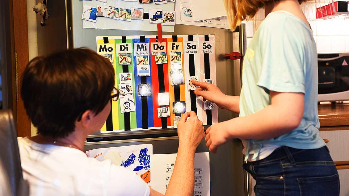 Karin Schmidt und Kerstin sortieren die Wochenaufgaben auf einem Plan am Kühlschrank.