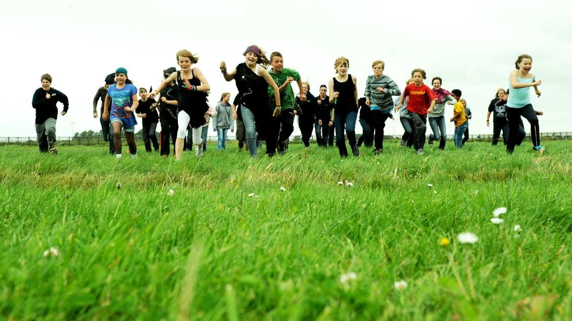 Kinder laufen über eine Wiese.