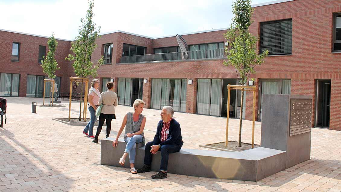 Hausleiterin Anke Flender und Pastoralreferent Ludger Picker sitzen vor dem Neubau auf einer Bank..