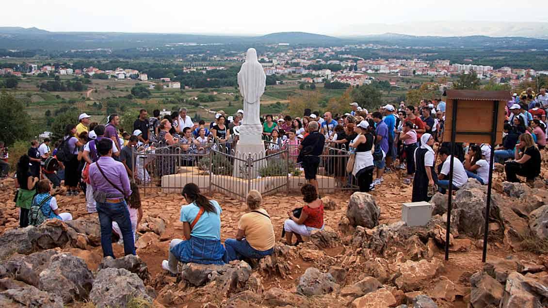 Pilger rasten an einer Statue der Muttergottes in Medjugorje.