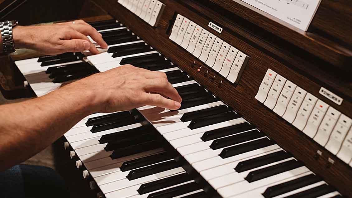 Hände eines Orgelspielers auf einer Orgel