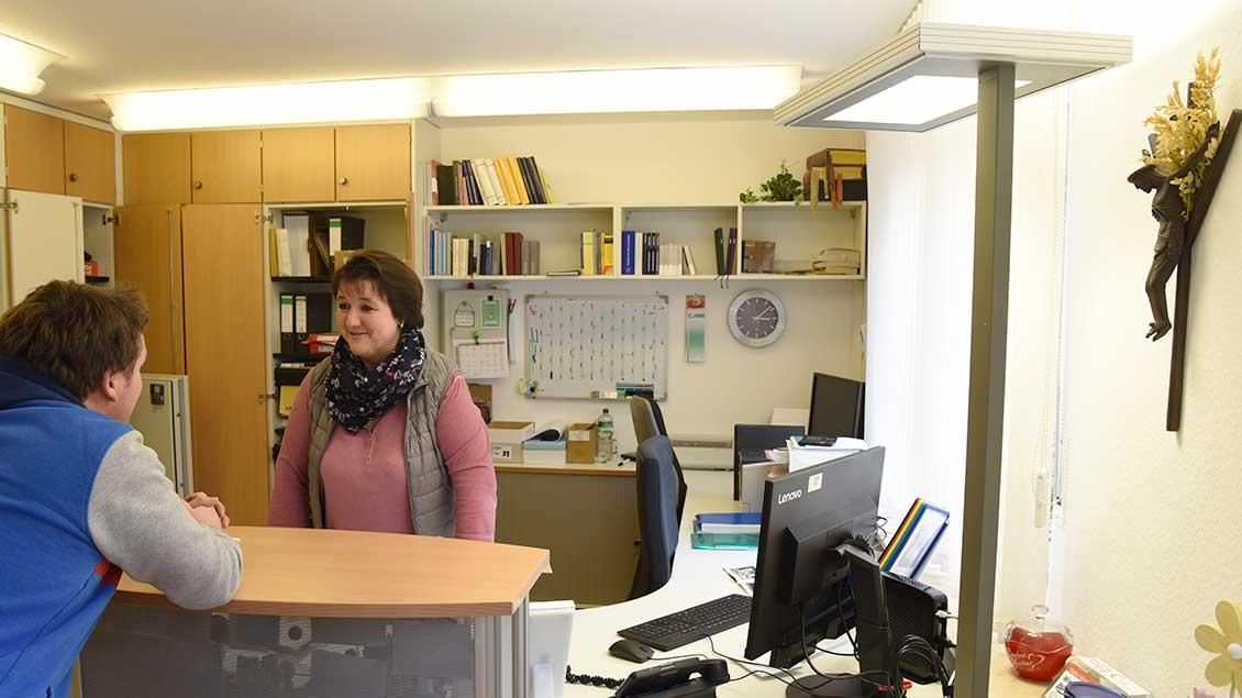 Pfarrsekretärin Tanja Antepohl steht in ihrem Büro und spricht mit einem Gast.