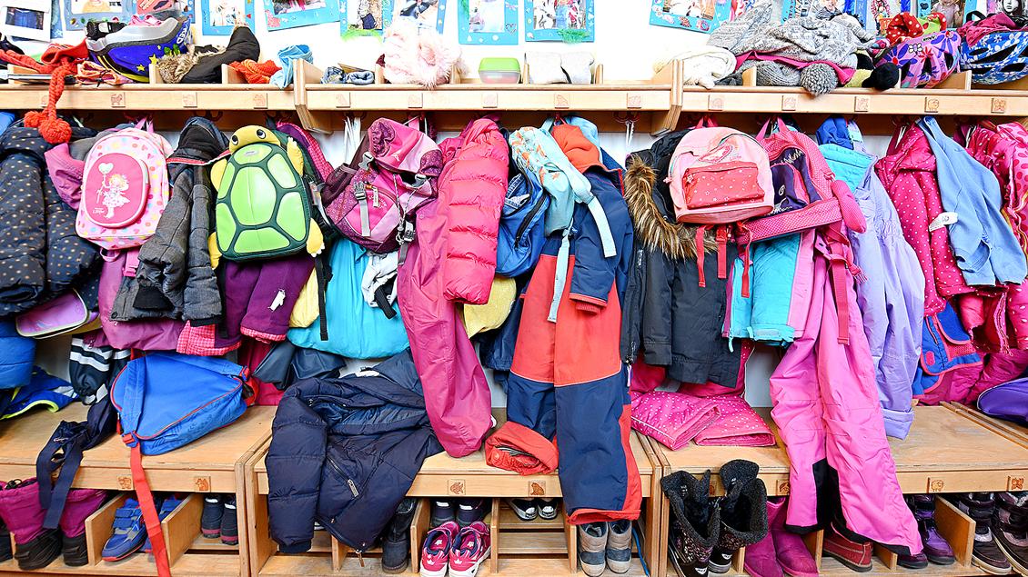 Eine Garderobe in einem Kindergarten voller Anoraks, Stiefel und Fahrradhelme.