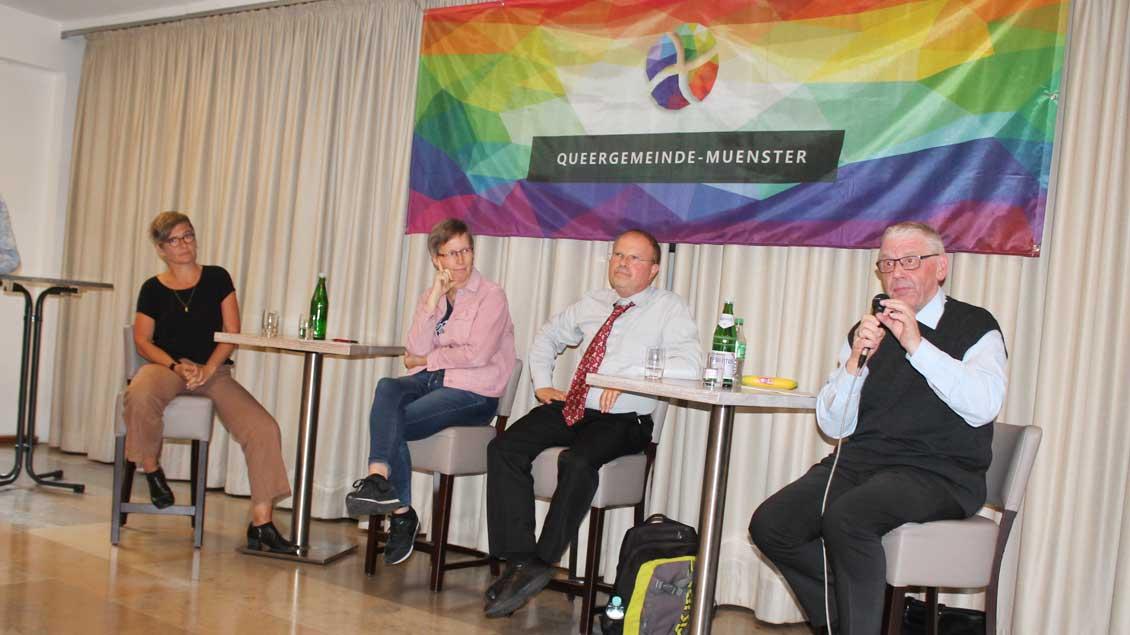 Vier Menschen diskutieren unter dem Banner der Queergemeinde Münster.