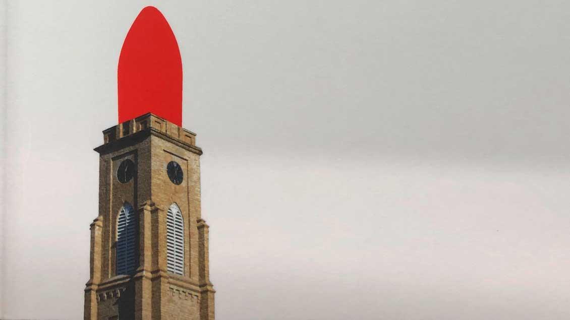Ein Kirchturm mit einer knallroten Lippenstift-Spitze.