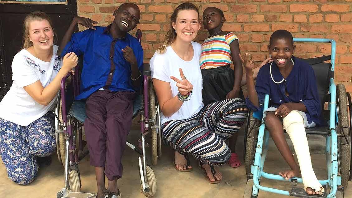 Marie Bußmann (links) und Juliane Kaiser sitzen neben ruandischen Kindern, die in Rollstühlen sitzen.