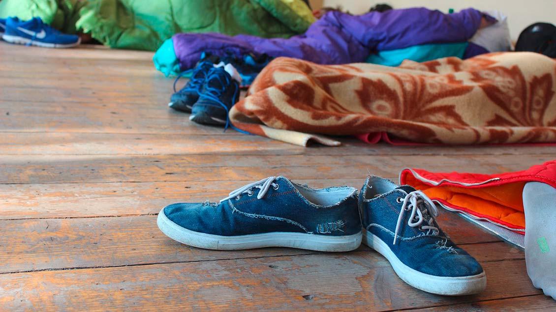 Schuhe und Schlafsäcke liegen auf einem Holzboden.