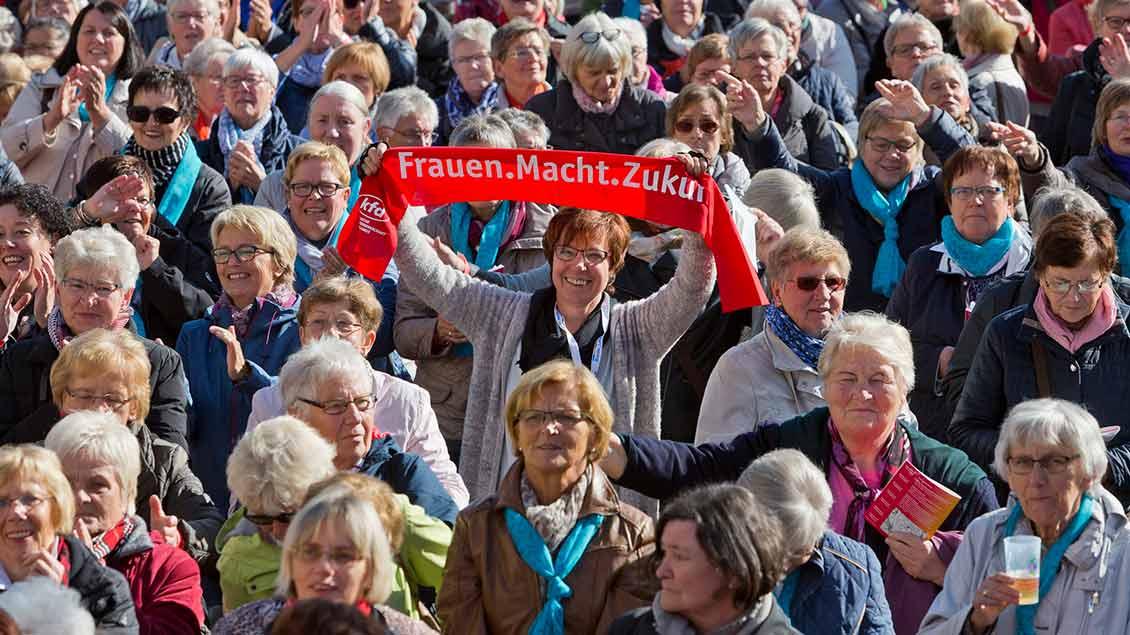 Münster 2018: Eine Frau inmitten vieler Frauen hält den KFD-Kampagnen-Schal in die Kamera.