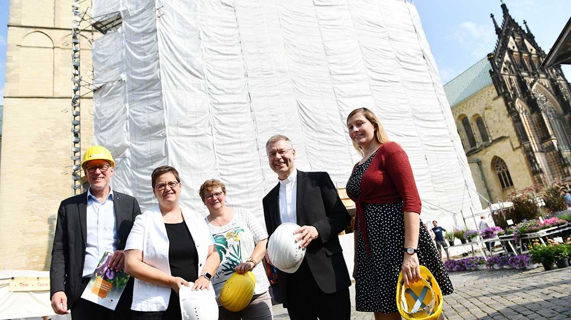 Vertreter des Kolping-Diözesanverbands präsentieren vor dem eingerüsteten Dom in Münster ihre Gebets-Initiative.