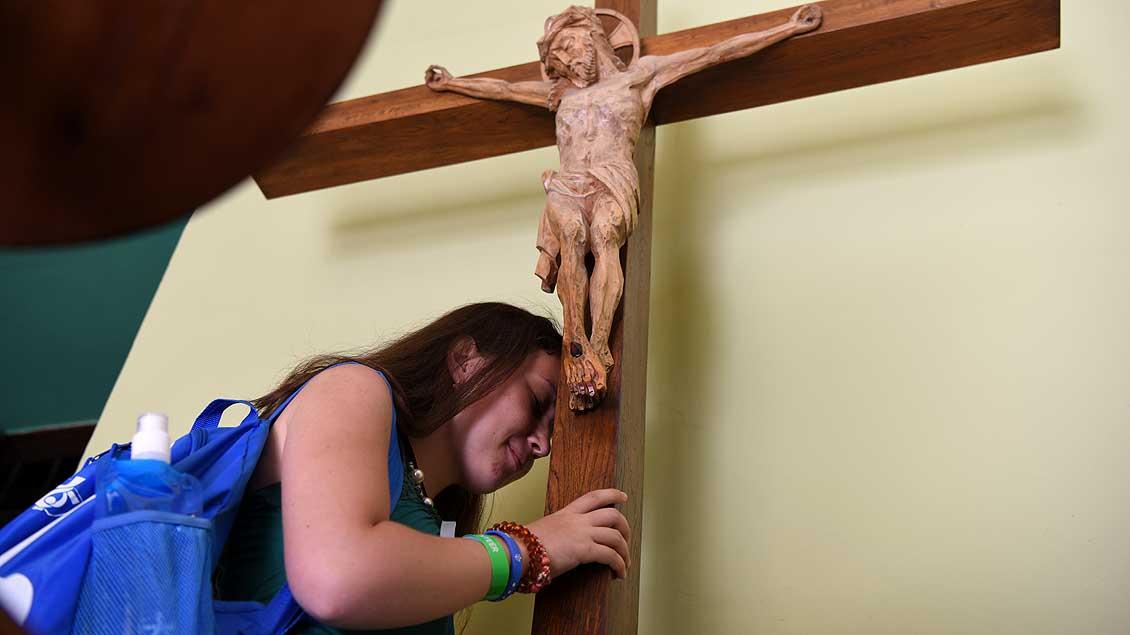 Junge Frau vor einem Kreuz