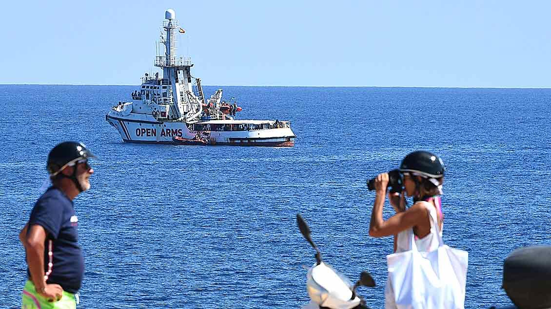 Eine junge Frau fotografiert einen Mann während im Hintergrund auf dem Meer das Rettungssschiff Opern Arms zu sehen ist.