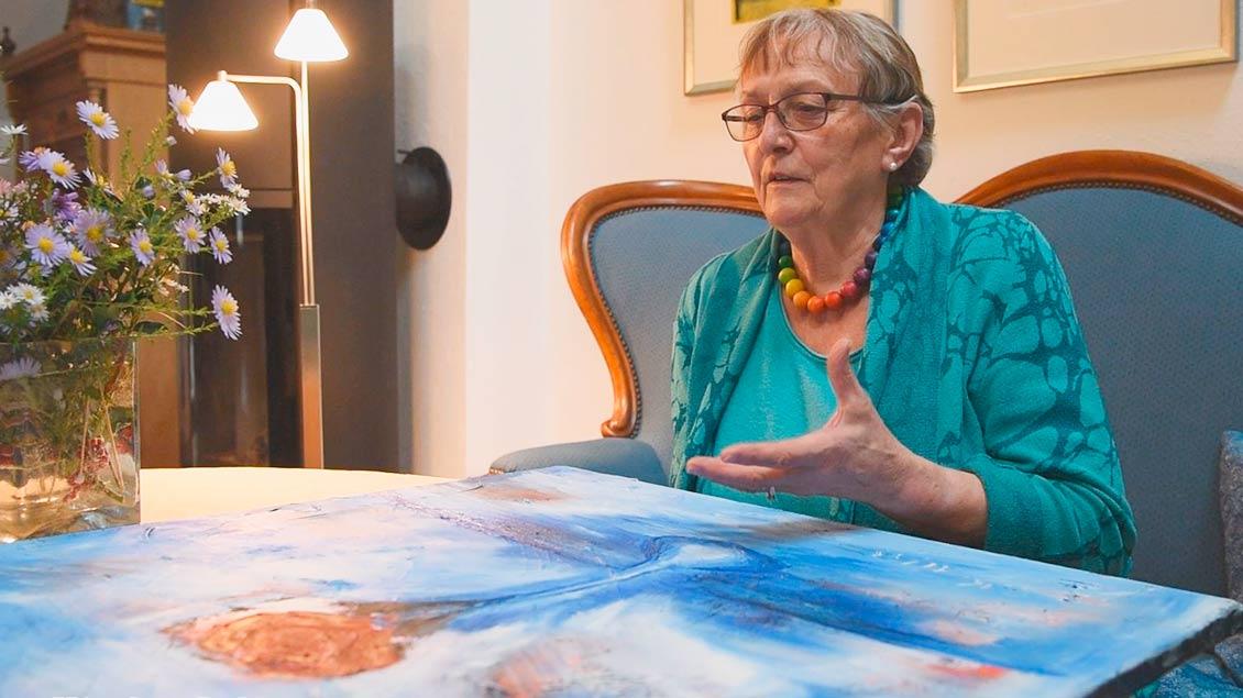 Margret Pernhorst sitzt auf ihrem Sofa und betrachtet ihr Rosenbild.