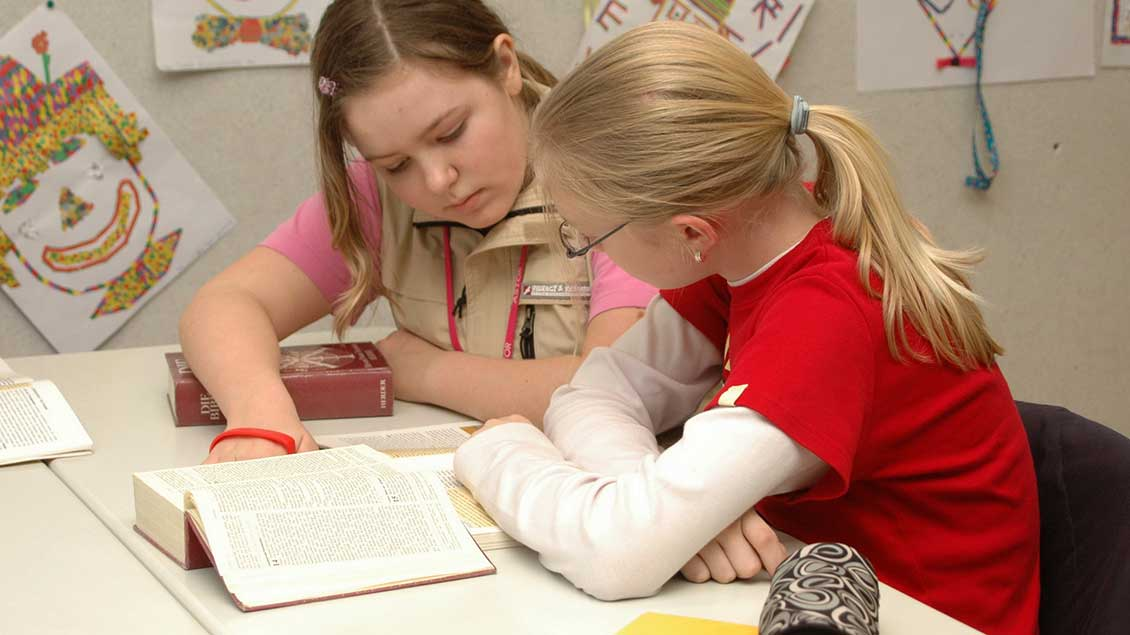 Zwei Schülerinnen schauen in eine Bibel