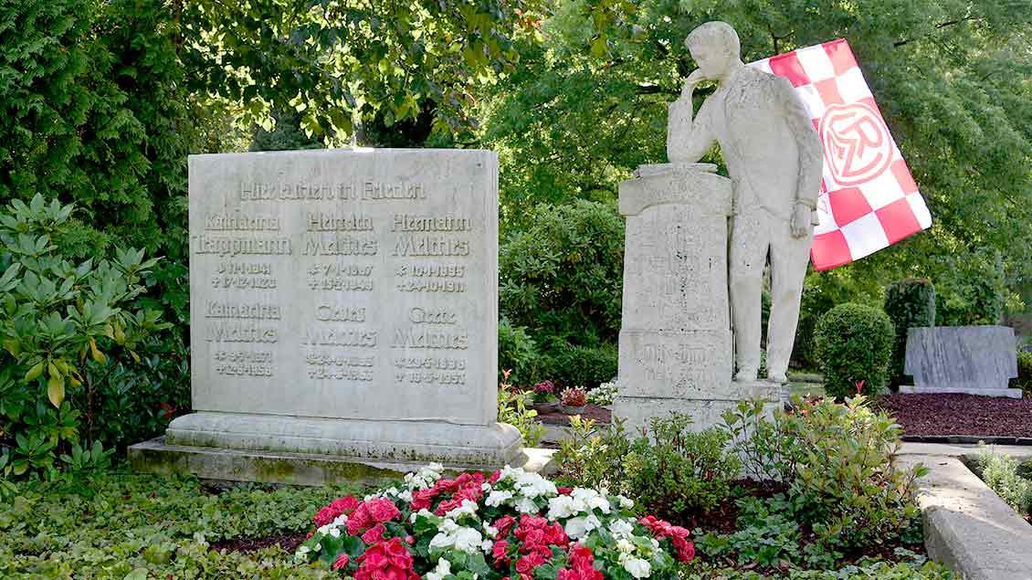 Das Grab des Vereinsgruenders des Fußballklubs Rot-Weiss Essen (RWE), Georg Melches, und seiner Familie. Dekoriert mit einer RWE-Fahne.