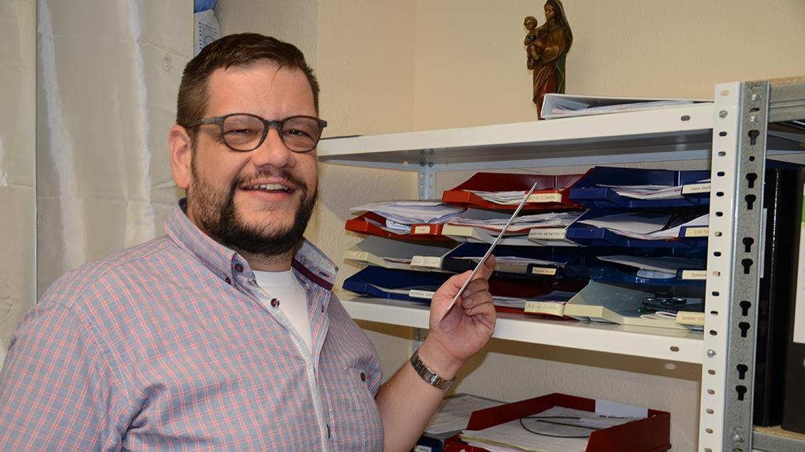 Martin Deckers steht vor einem Regal mit Unterlagen.