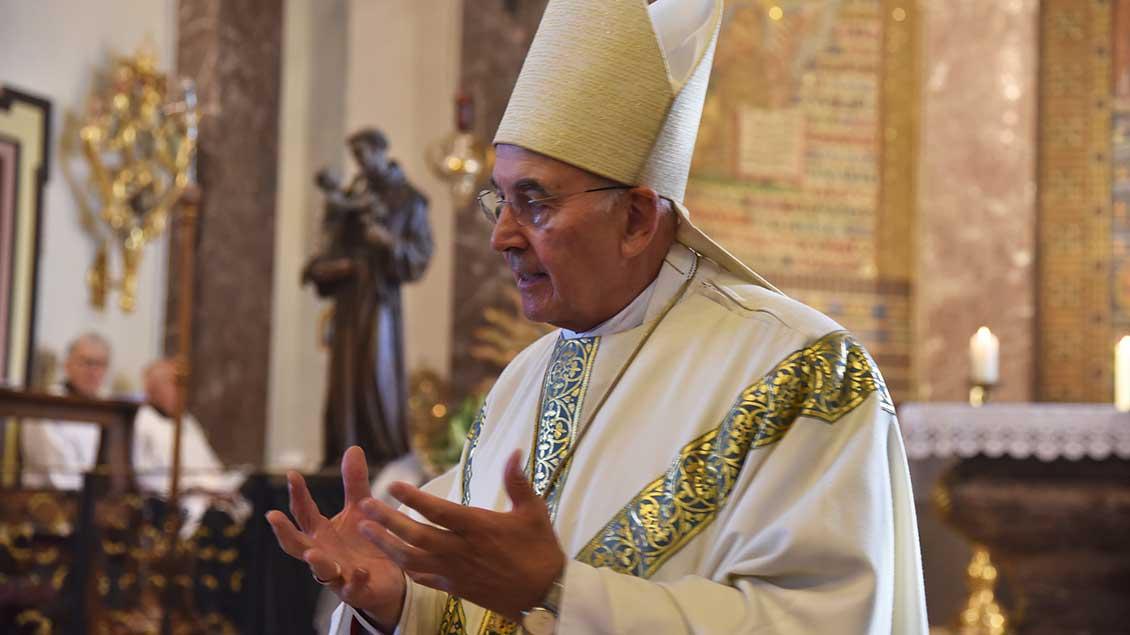 Bischof Genn erzählt den Kindern in der Predigt vom heiligen Antonius von Padua, dessen Figur im Hintergrund zu sehen ist.