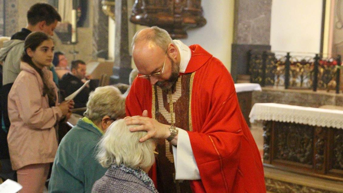 Pfarrer Dirk Költgen segnet kranke und behinderte Menschen bei einer Wallfahrt. | Foto: Nina Holstermann