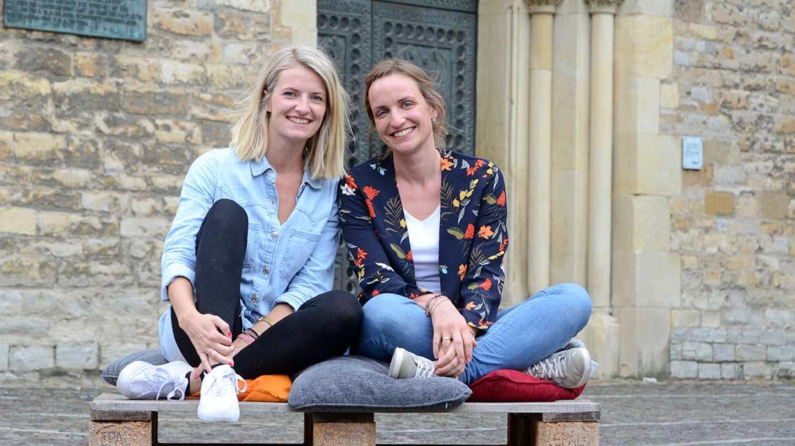 """Christine Pleye und Franzis Niehoff sitzen vor der Jugendkirche """"Effata"""" in Münster."""