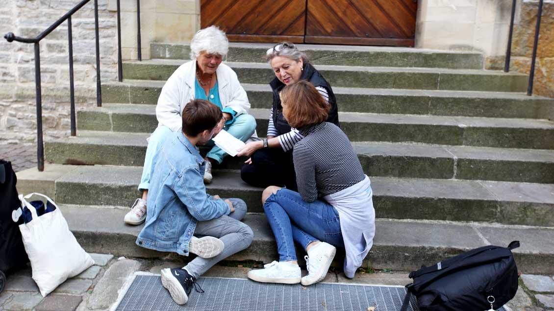 Vier Menschen unterhalten sich auf den Stufen des Doms in Münster.