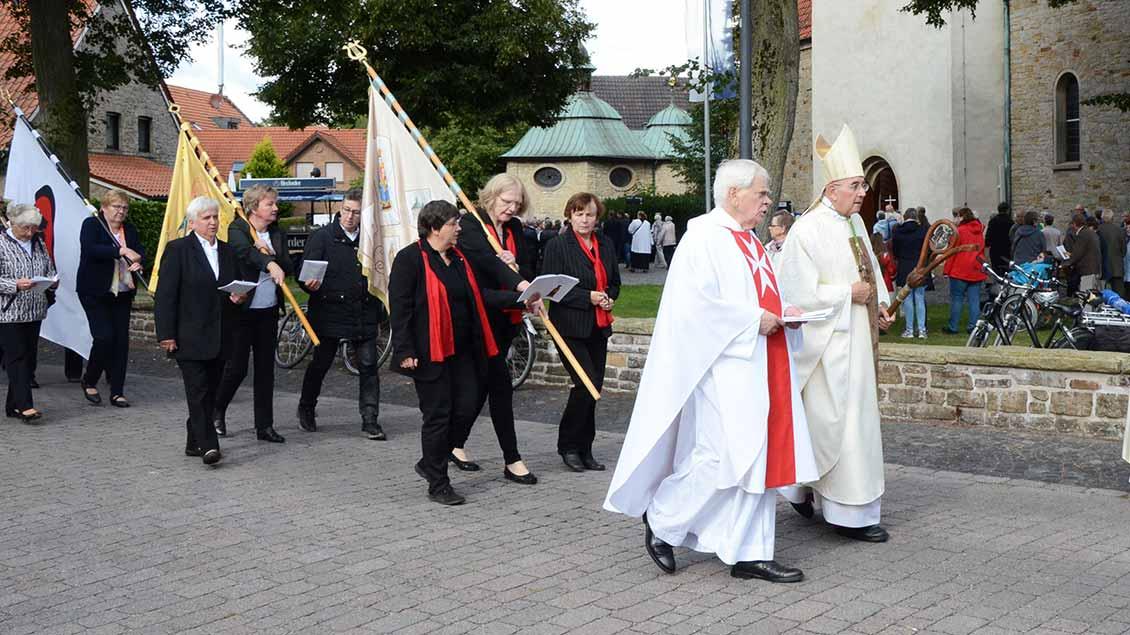 Bischof Genn mit Malteser-Diözesanseelsorger Josef Leenders und Fahnenabordnungen