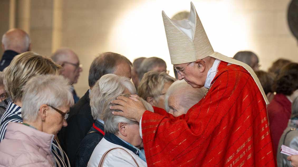 """Bischof Felix Genn legt Trauernden am """"Begegnungstag für Hinterbliebene"""" die Hände auf und spendet den Segen."""