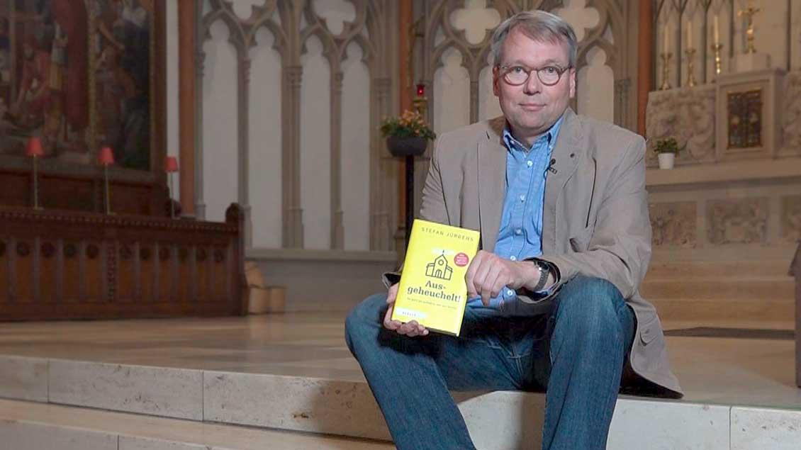 """Pfarrer Stefan Jürgens auf den Stufen im Altarraum der Heilig-Kreuz-Kirche in Münster. In den Händen hält er sein neues Buch """"Ausgeheuchelt""""."""