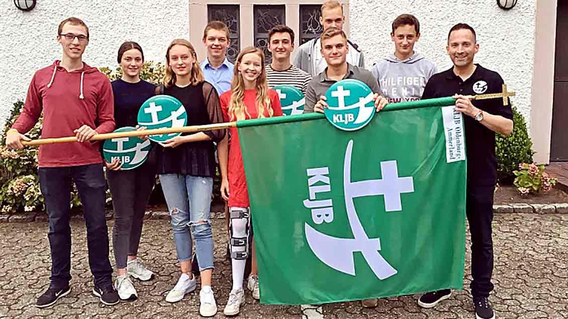 Pfarrer Jan Kröger und der Vorstand der neuen KLJB-Ortsgruppe Oldenburg-Ammerland mit der grün-weißen KLJB-Fahne.