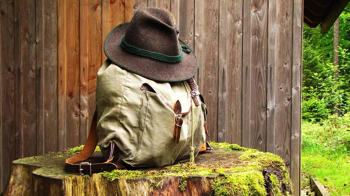 Ein Wanderrucksack mit einem Hut auf einem abgesägten Baumstamm in der Natur.