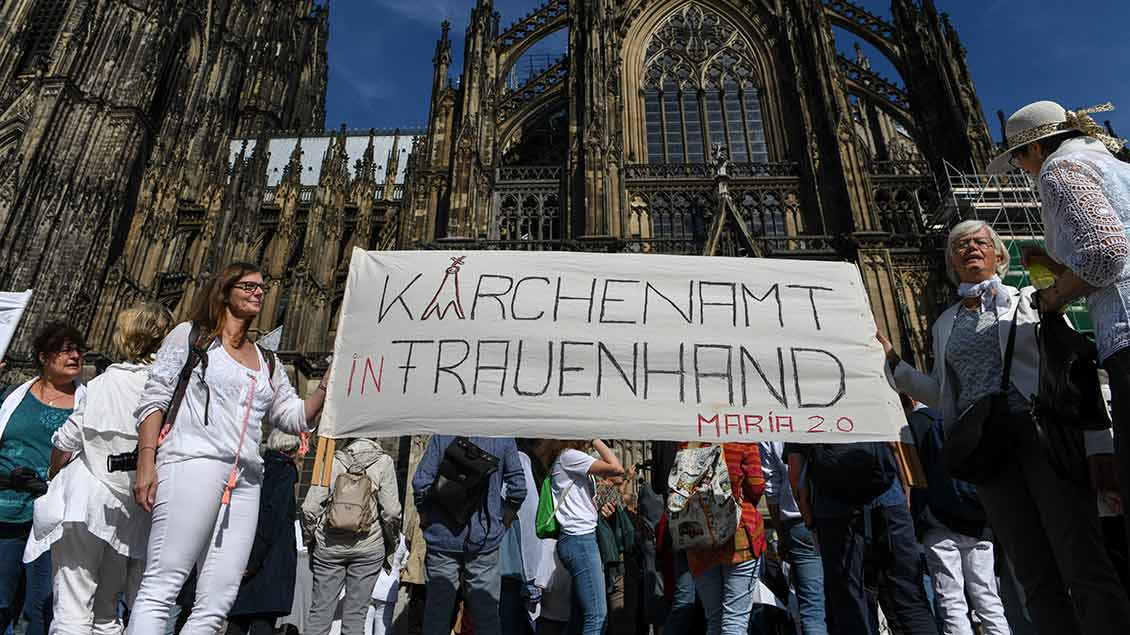 "Frauen halten vor dem Kölner Dom ein Banner mit der Aufschrift ""Kirchenamt in Frauenhand"" bei einer Demonstration der Initiative Maria 2.0 am 22. September 2019 in Köln. Foto: Harald Oppitz (KNA)"