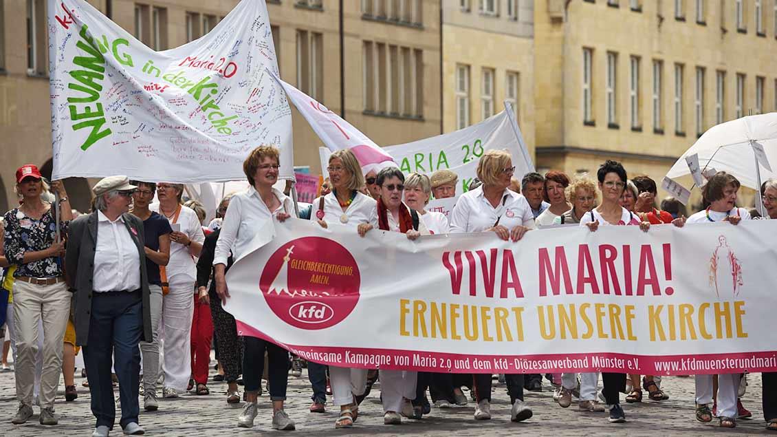 """Frauen von """"Maria 2.0"""" protestieren mit Plakaten."""