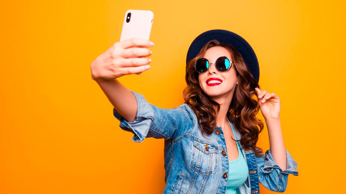 Eine junge Frau macht ein Selfie mit dem Handy
