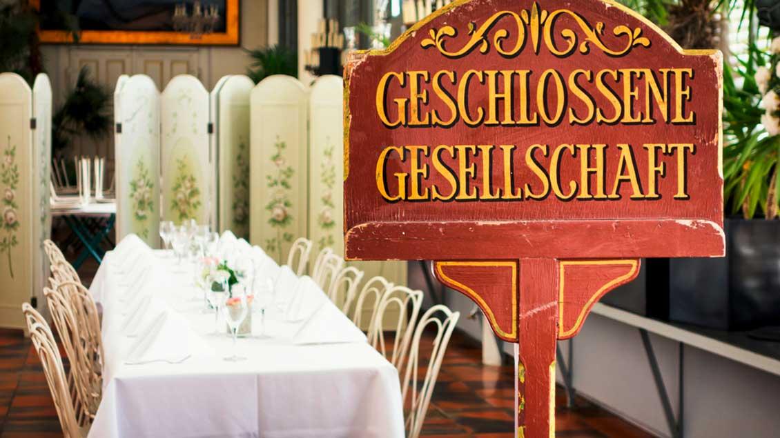 """Ein festlich gedeckter Tisch mit einem Schild """"Geschlossene Gesellschaft"""" davor. Foto: FoTToo (Shutterstock)"""