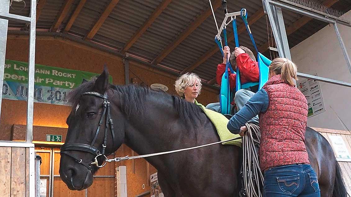 Eine Frau wird mit einem Kran auf ein schwarzes Pferd gehoben.