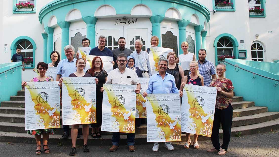 Organisatoren des Abrahamsfestes mit Plakaten
