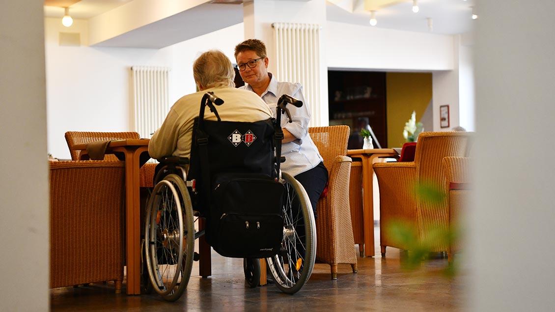 Krankenhaus-Pastoralreferentin Andrea Greshake im Gespräch mit einer Altenheimbewohnerin, die im Rollstuhl sitzt.