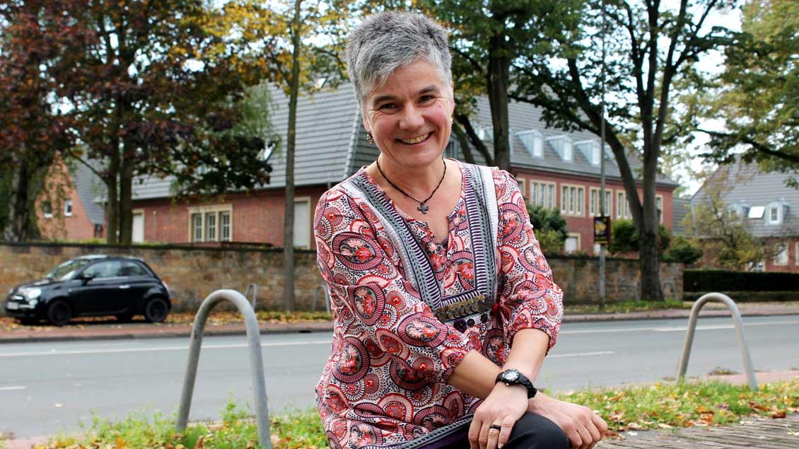 Astrid Brückner sitzt auf einer Mauer.