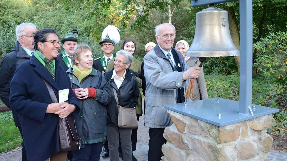"""Bernhard Lübbering läutet die Friedensglocke im """"Garten der Religonen"""" in Recklinghausen."""