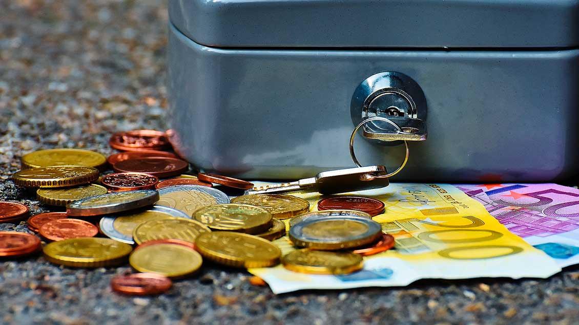 Münzen und Geldscheine neben einer Geldkassette.