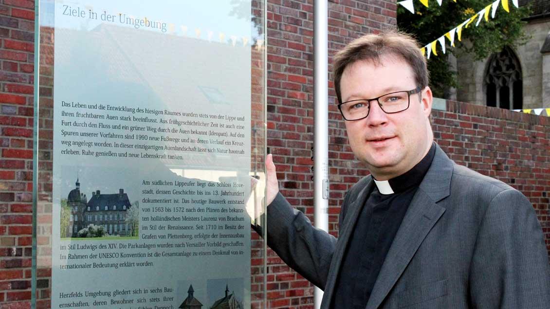 Pfarrer Joachim Kosmann vor einer Glasstele in der Dorfmitte von Herzfeld..