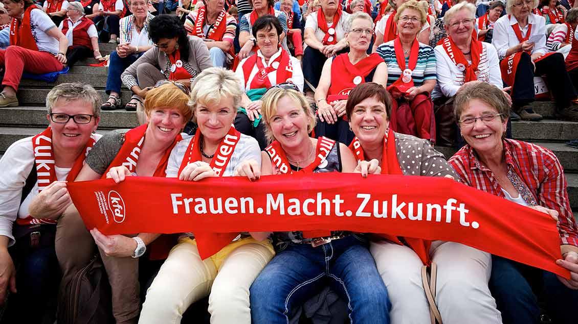 """Frauen halten einen roten Schal mit dem Motto der Mitglieder-Werbekampagne """"Frauen.Macht.Zukunft"""" hoch."""