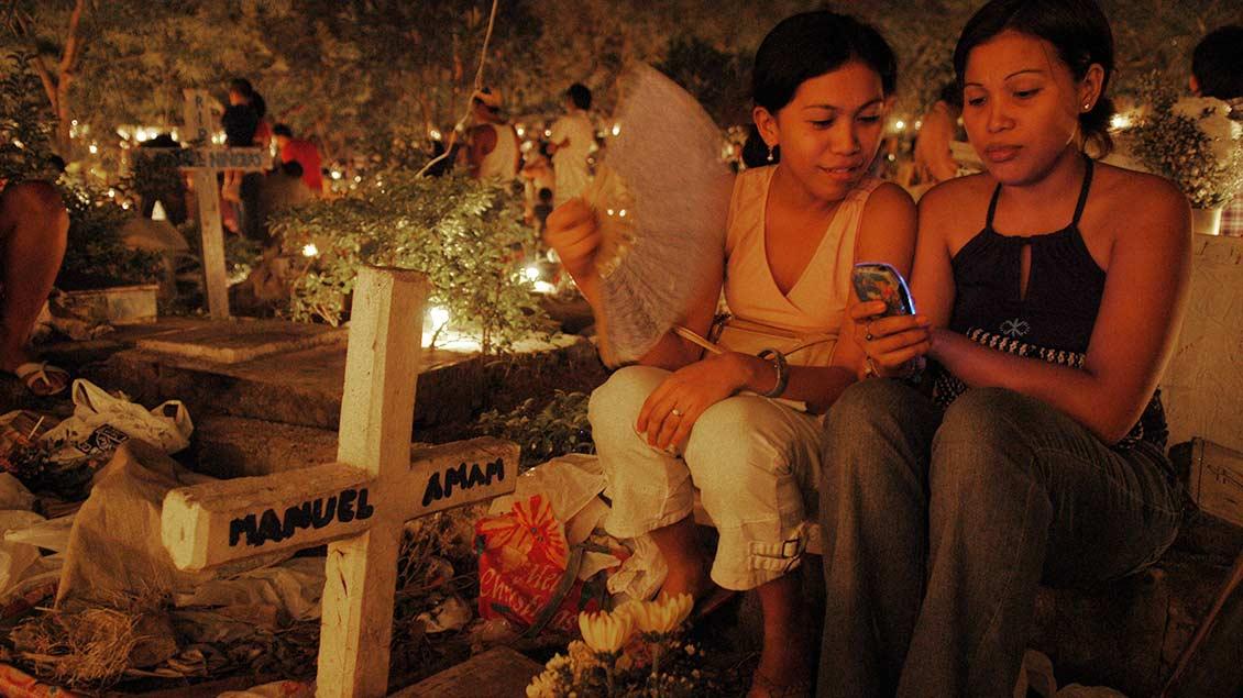 Zwei jungen Frauen sitzen am Grab eines Verwandten auf einem Friedhof Friedhof in Cebu-City auf den Philippinen.
