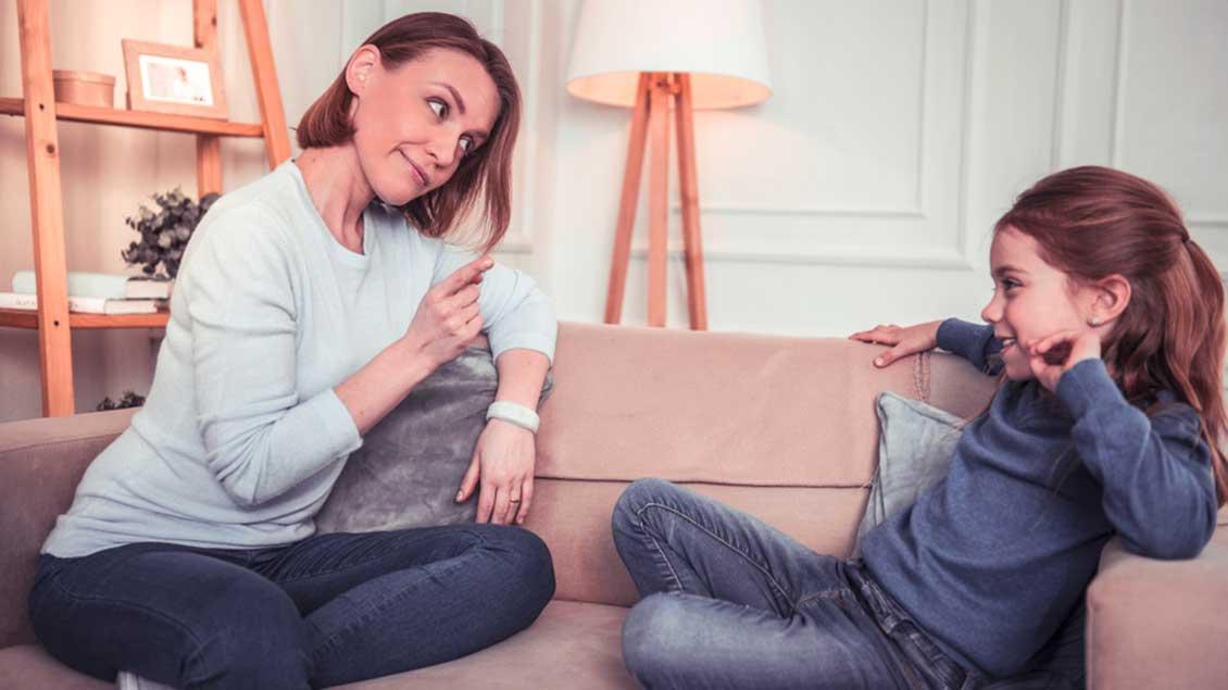 Eine Mutter mit erhobenem Zeigefinger spricht zu ihrer Tochter.