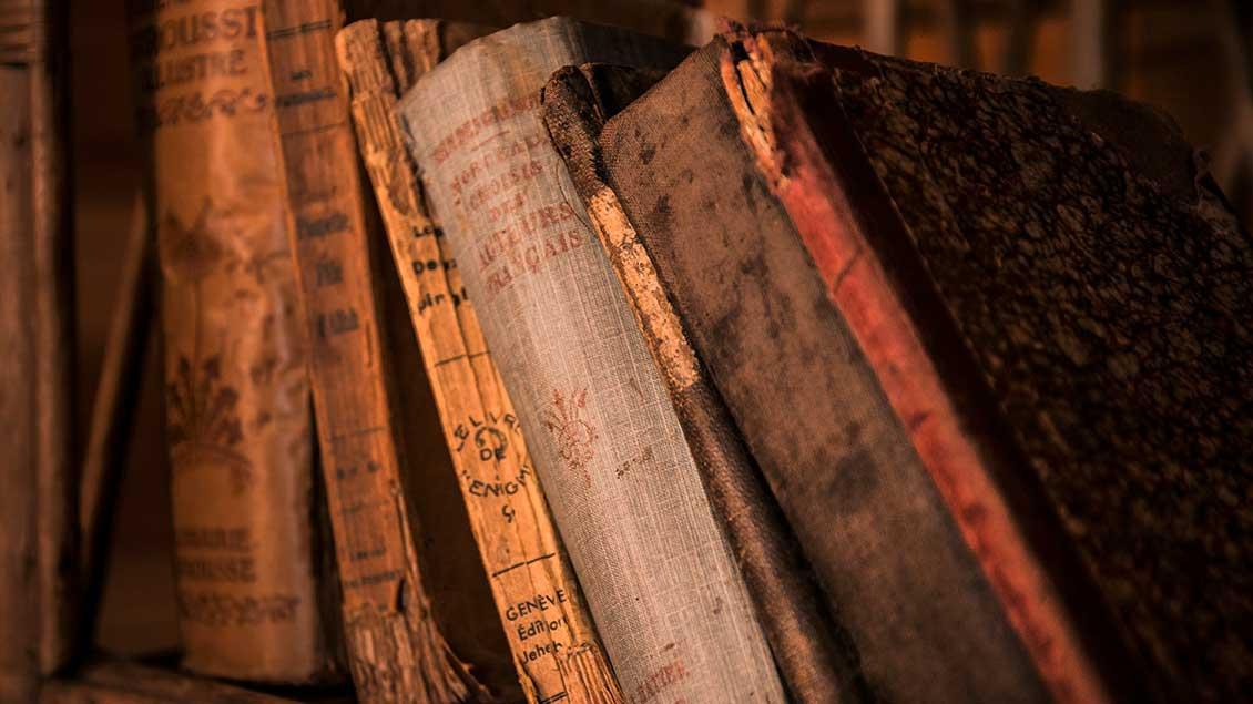 Alte Bücher stehen im Regal.