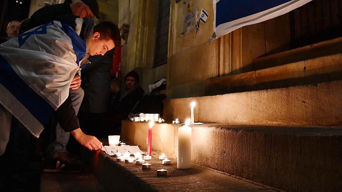 Ein junger Mann mit einer Israel-Flagge entzündet eine Kerze.