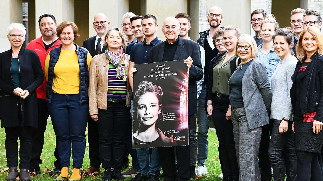 Bischof Felix Genn steht mit einem Plakat der Arbeitgeber-Kampagne unter vielen Mitarbeiter, die als Foto-Models bei der Kampagne mitgemacht haben.